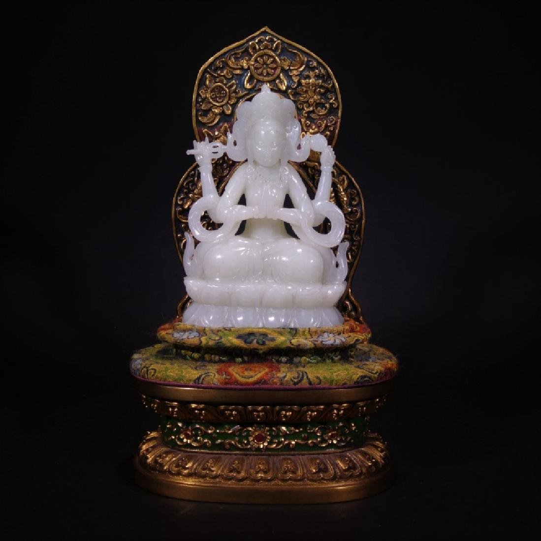A CARVED HETIAN JADE SEATED GUANYIN FIGURE