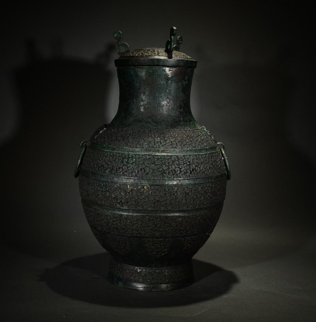 A BRONZE CARVING WINE VESSEL WITH LID