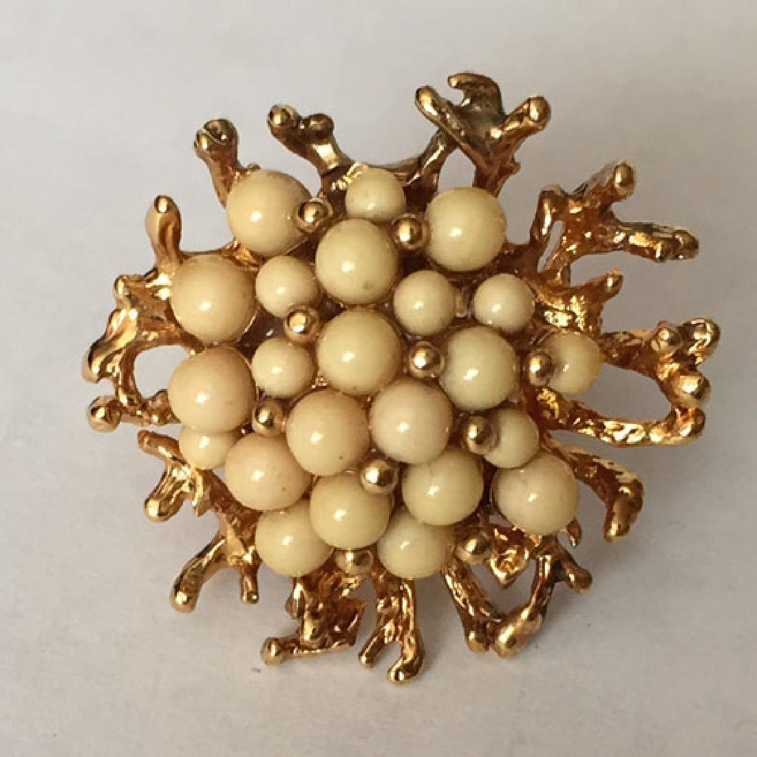 Gold plated ring with cream color beads in the middle,