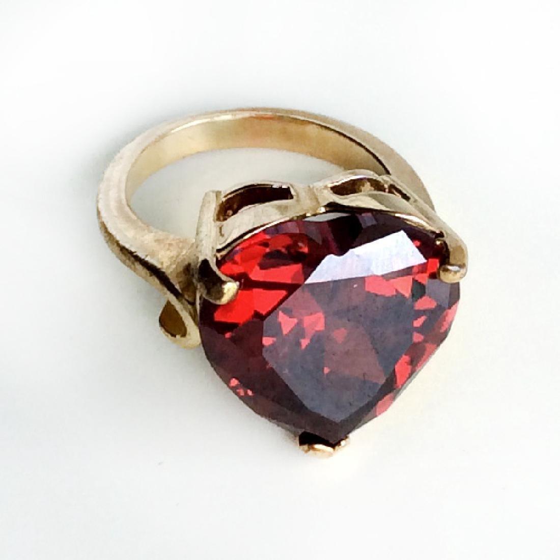 Gold tone heart shaped prongs set faceted garnet color