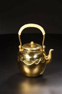A CARVED GILT-SILVER TEAPOT AND COVER.ANTIQUE
