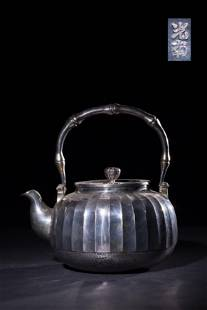 A CARVED SILVER TEAPOT AND COVERANTIQUE