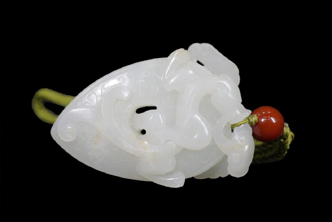 A CARVED WHITE JADE DRAGON PENDANT