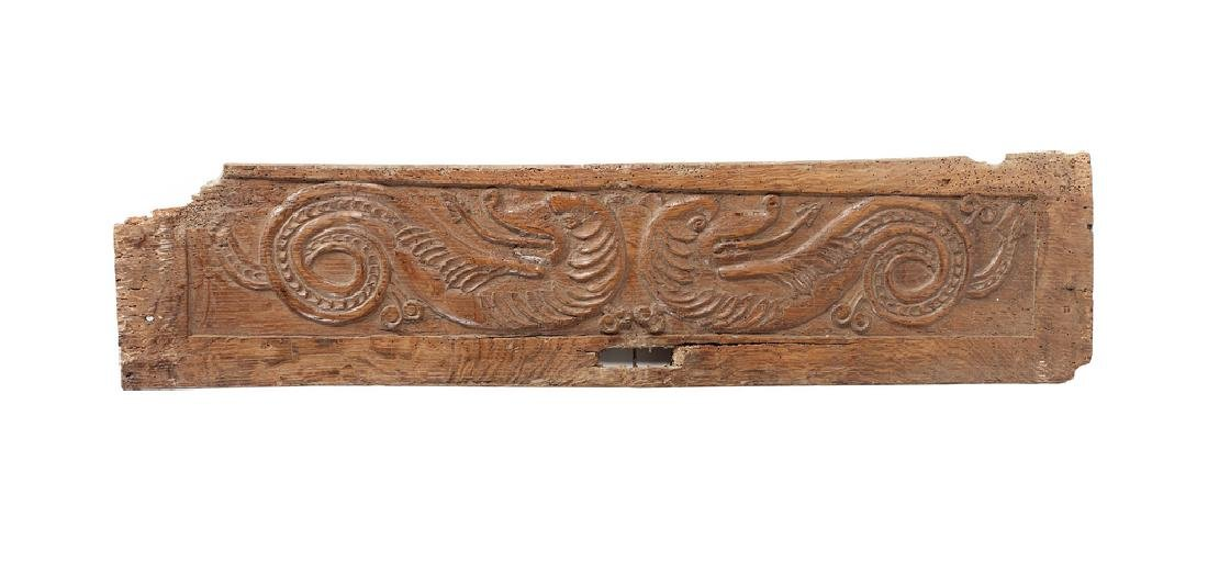 A Charles I oak architectural panel carved with dragons
