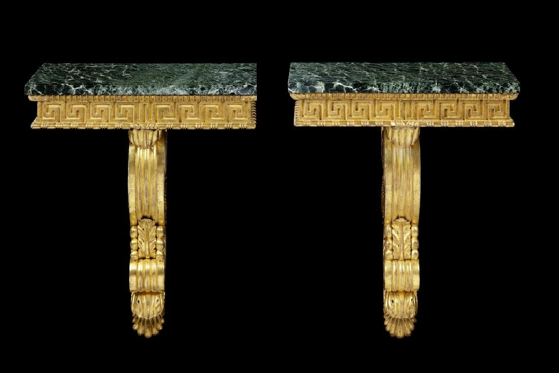 A pair of carved giltwood console tables/brackets