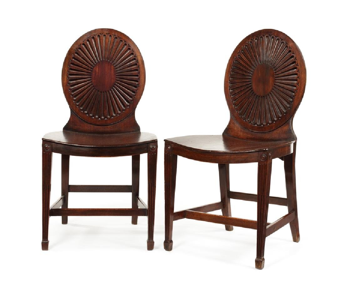 A pair of George III carved mahogany hall chairs