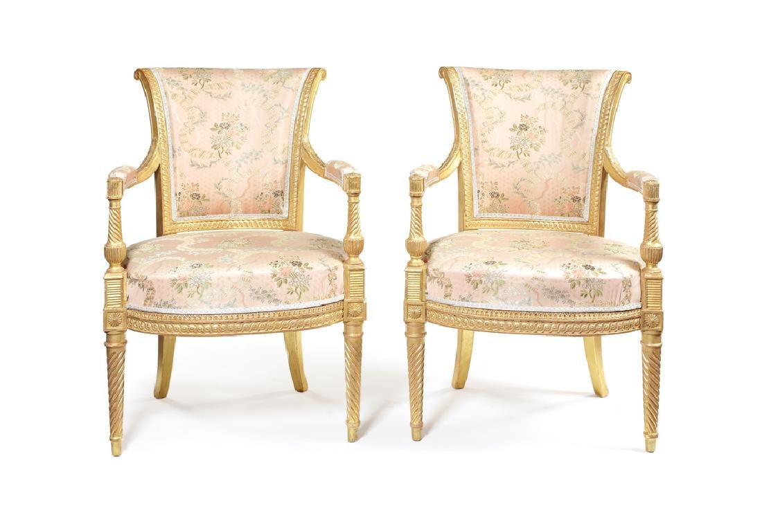 A pair of George III carved giltwood open armchairs