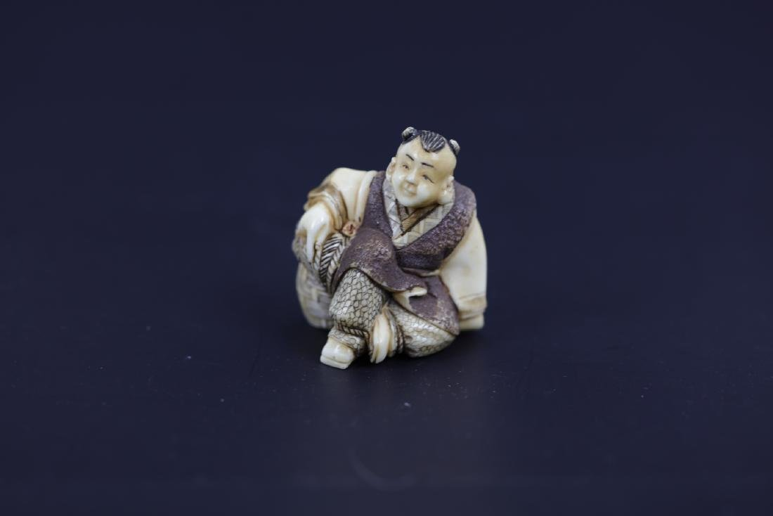 A Carved Netsuke of A Boy sitting Next To A Busket