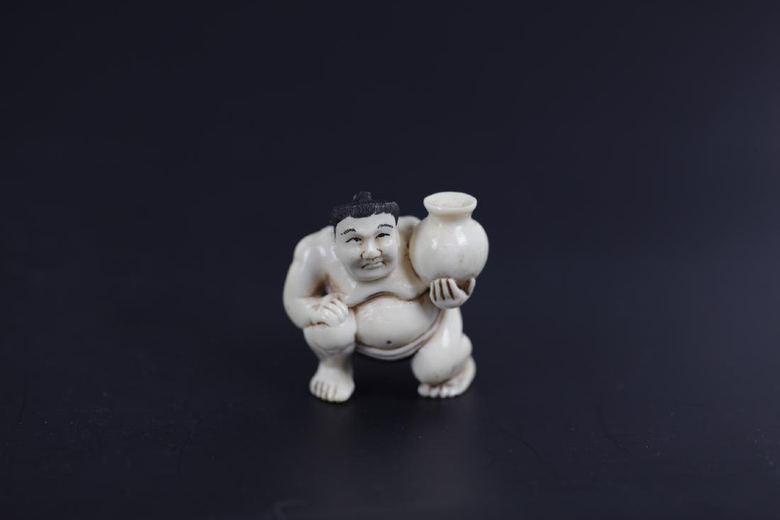 A Carved Netsuke of A Sumo Warrior Holding A Vase