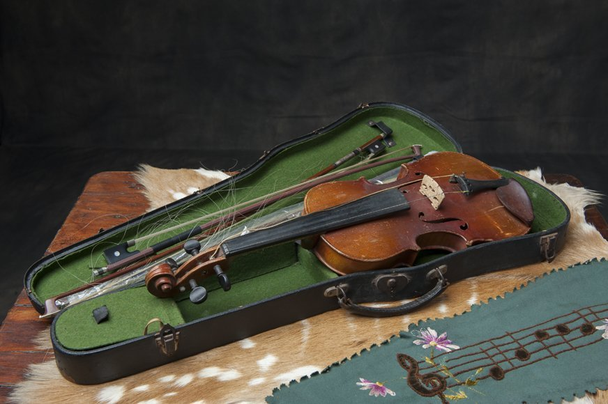 Old violin with spare strings and bows