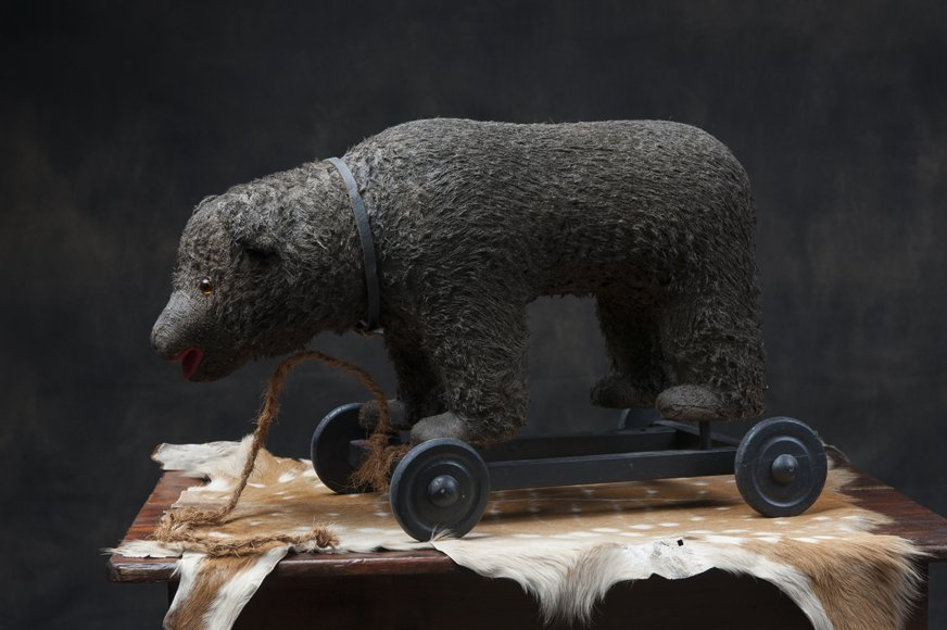 Antique toy bear on wheels
