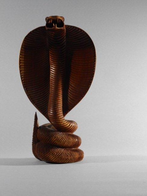 Handcarved wooden statue of a cobra snake