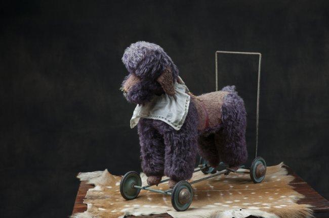 Antique toy poodle on iron wheels