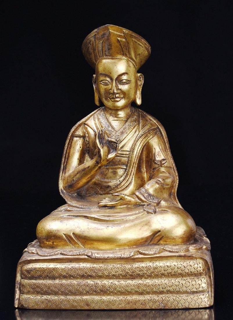 A GILT-BRONZE FIGURE OF GURU