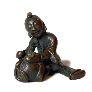 A SMALL BRONZE BOY PAPERWEIGHT LATE MING EARLY QING