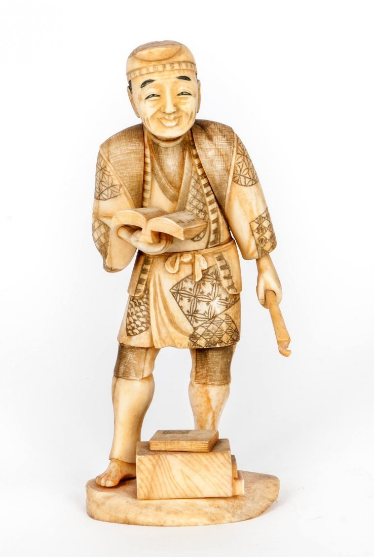 An Antique Japanese Carved Ivory Figure Holding a Book