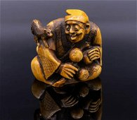 A Carved Stained   Netsuke of Man Playing with a