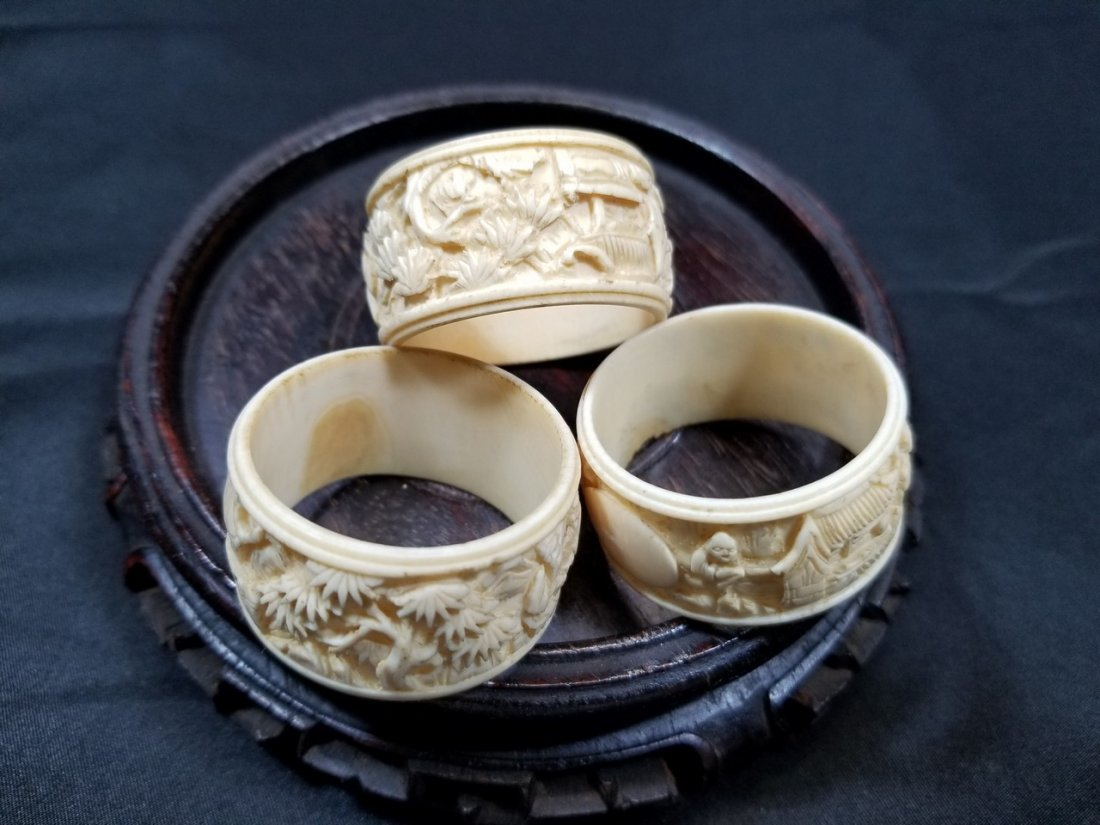 Three old ivory color carved napkin rings