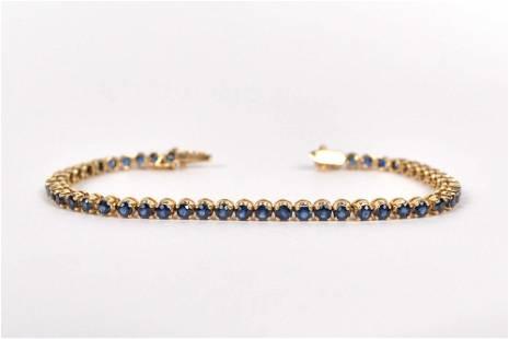 14K yellow gold tennis bracelet set with sapphires,