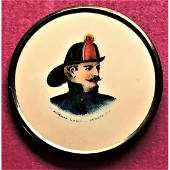 A FRAMED AMERICAN BUTTON DEPICTING A FIREMAN ON IT