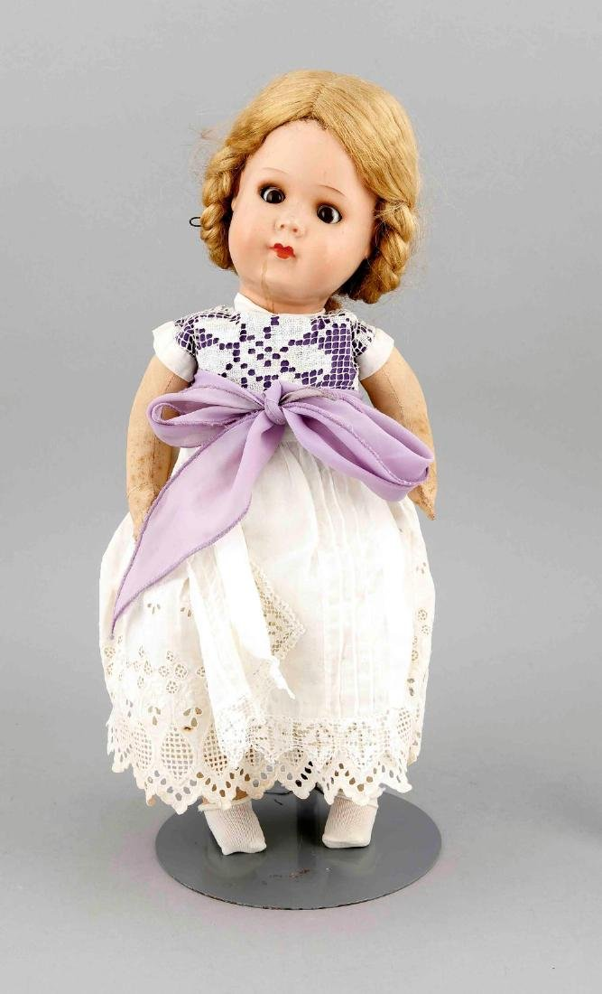 A doll with fabric body, the head presumably plastic,
