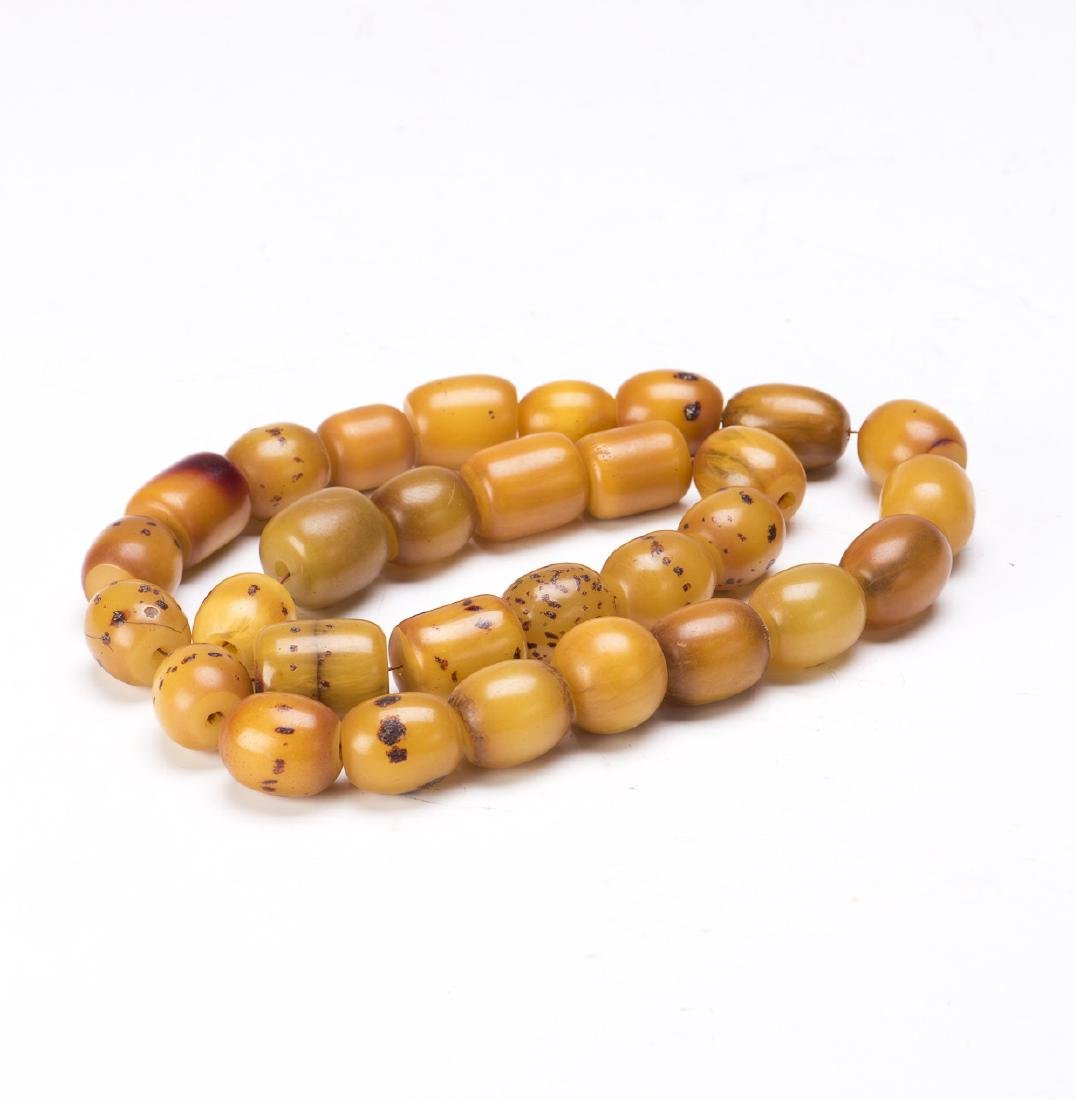 A STRAND OF BEESWAX BEADS, 30 BEADS