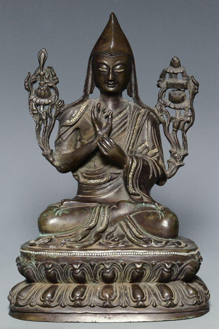 A QING DYNASTY SILVER-INLAID BRONZE FIGURE OF LAMA