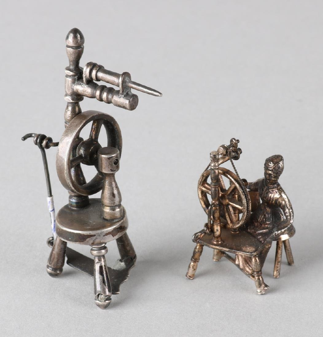 Two silver miniatures, 835/000, a spinning wheel and a woman behind a spinning w
