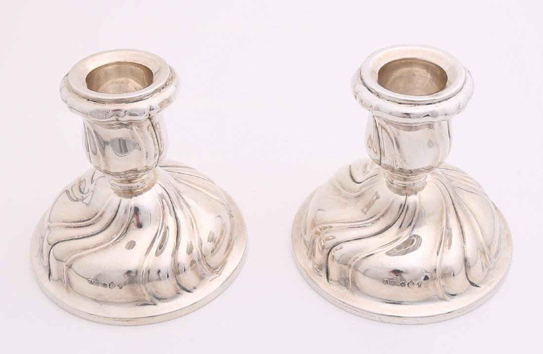 Two silver candlesticks, 835/000. Two low table candlesticks on a round base wit
