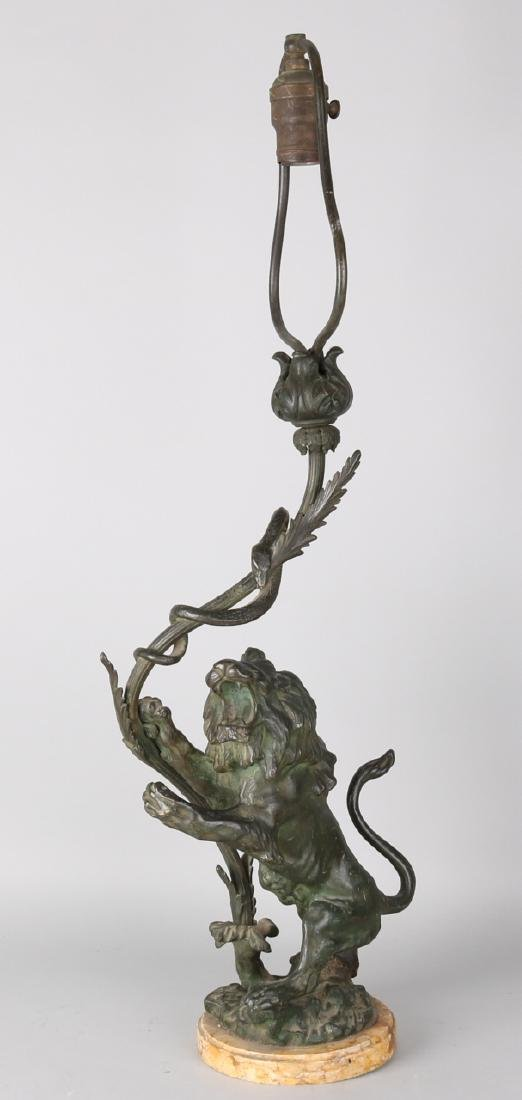 Antique bronze table lamp with male lion and snake, marble base. Circa 1910. In