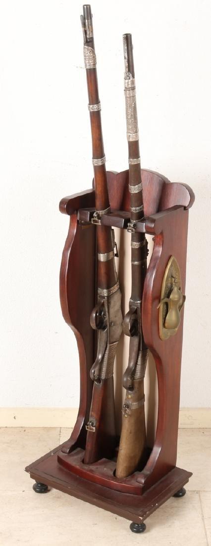 Two 19th century colonial rifles with gun rack. One Field Rifle Co. Birmingham E