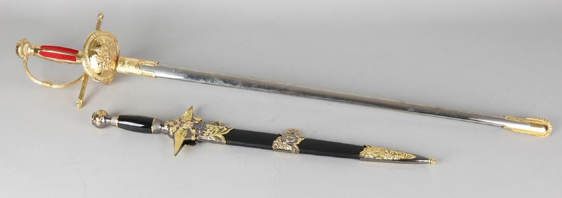 Two decorative blank gold plated ornamental weapons. One saber. One dagger. In s