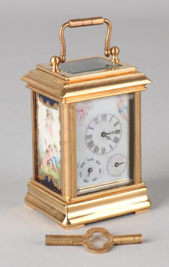 Small old brass travel alarm clock with day and date display and porcelain plaqu