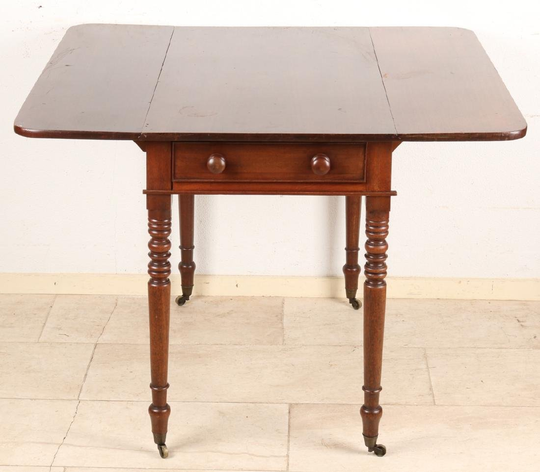 19th Century English mahogany folding table on brass wheels. A scratch. Size: 74