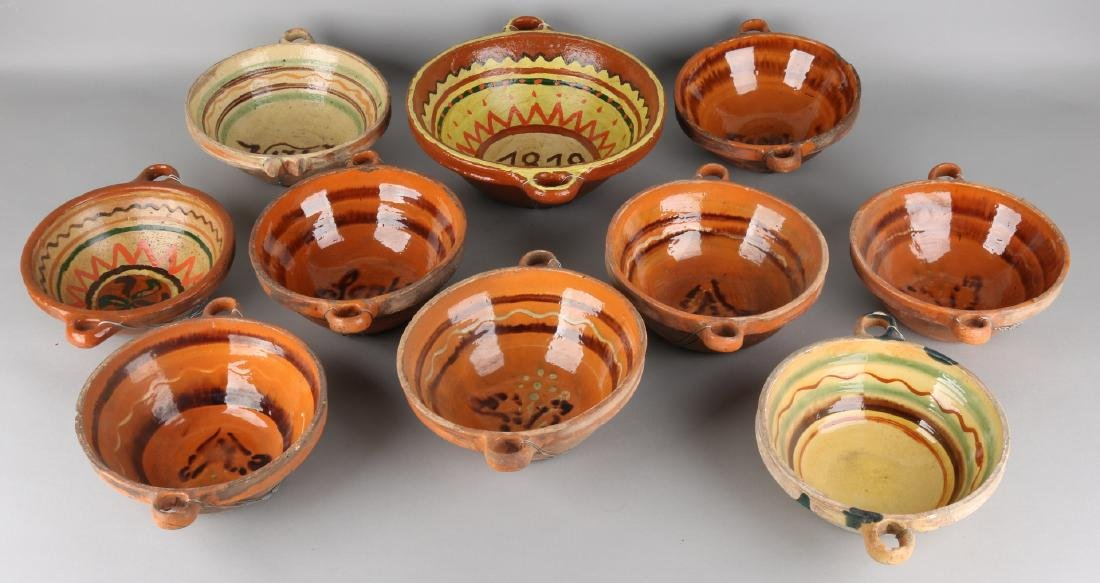 Ten pieces of 19th century German terracotta ceramic oven dishes with painted un