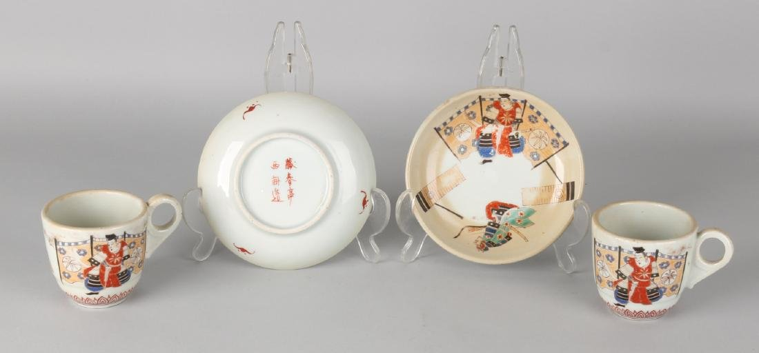 Two antique Japanese or Chinese cups and saucers with floor mark, figures and ba