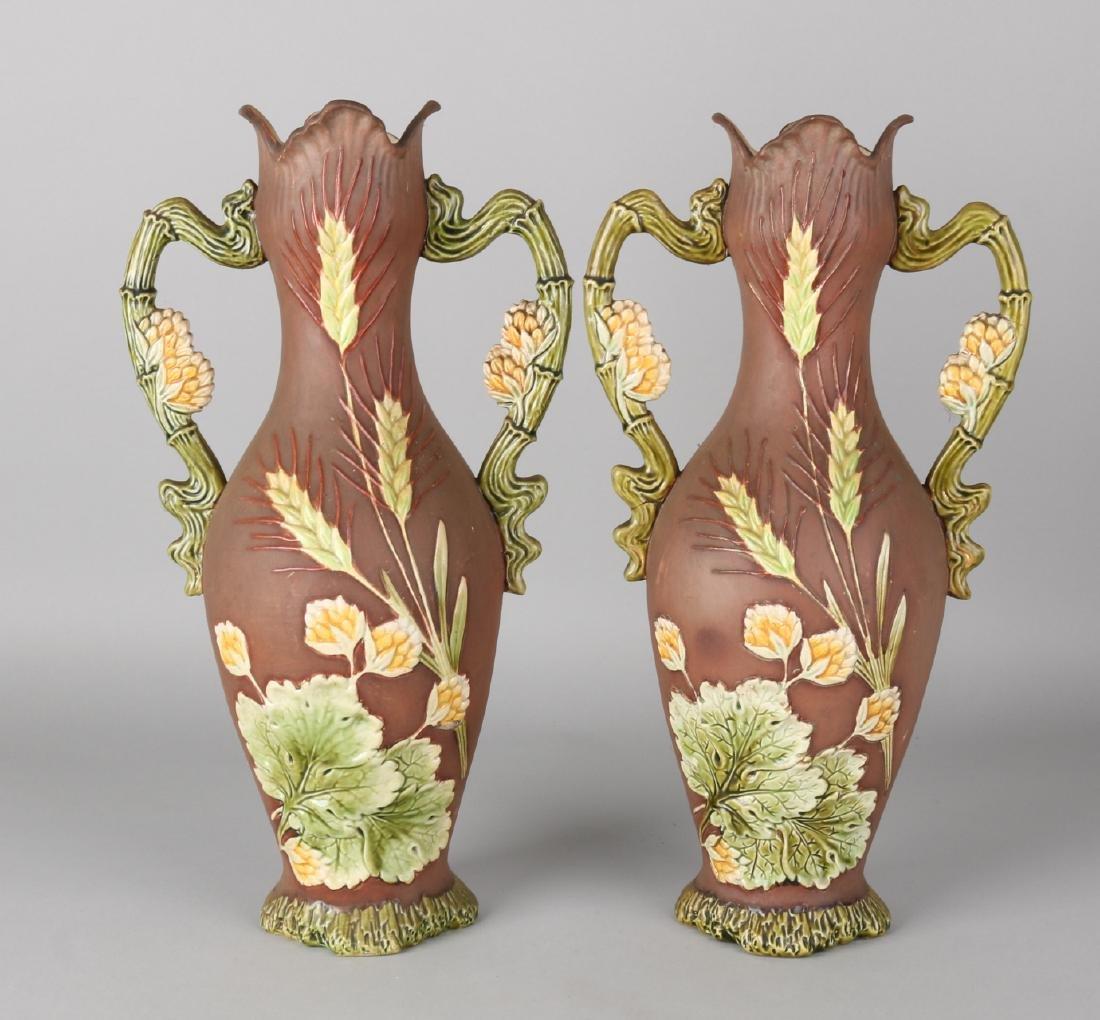 Two antique Jugendstil Majolica vases with floral decors on matt brown glaze. No