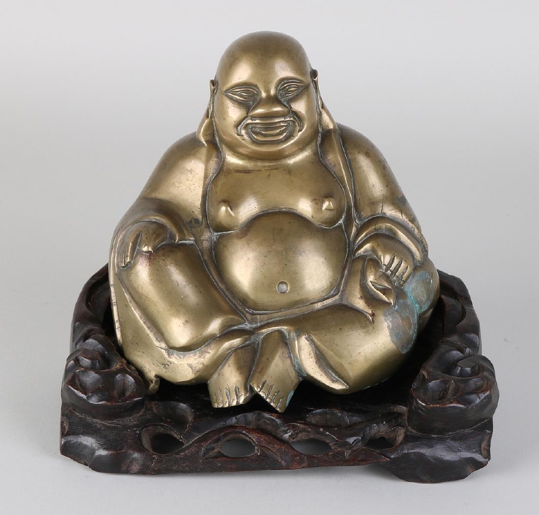 Ancient Chinese bronze Buddha on wood-burning base.