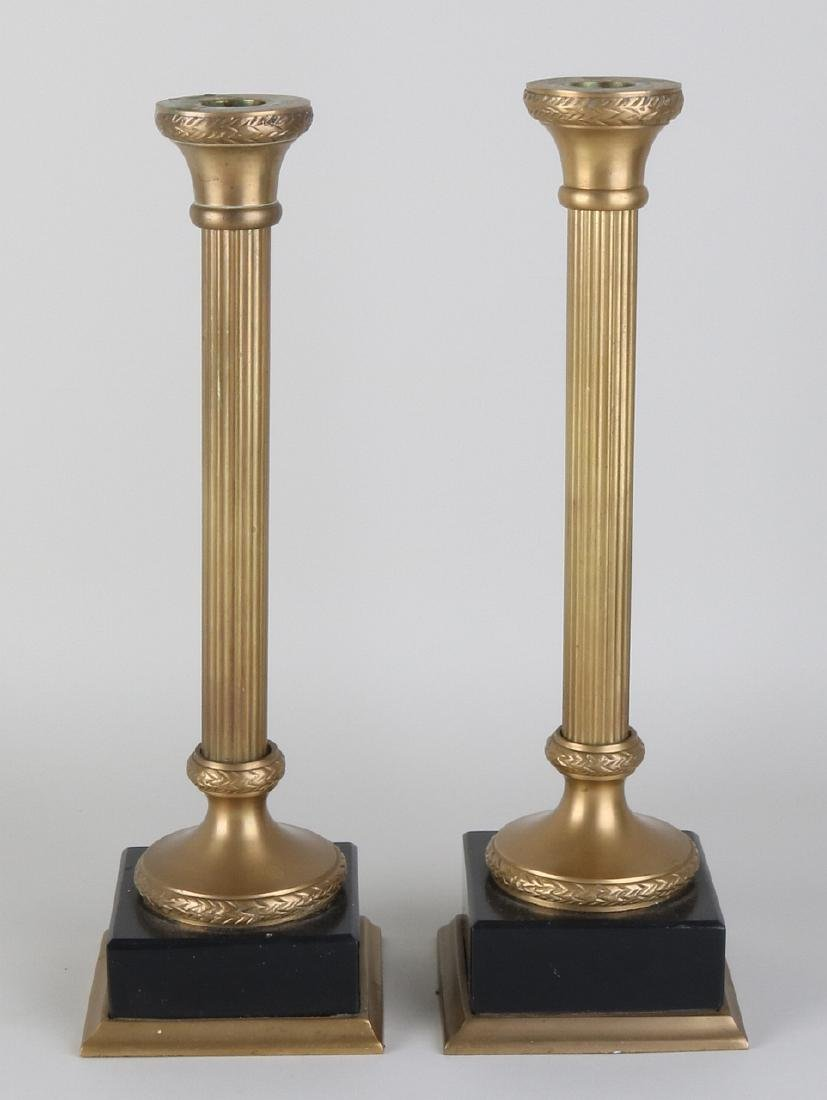 Two decorative brass candle holders with black marble