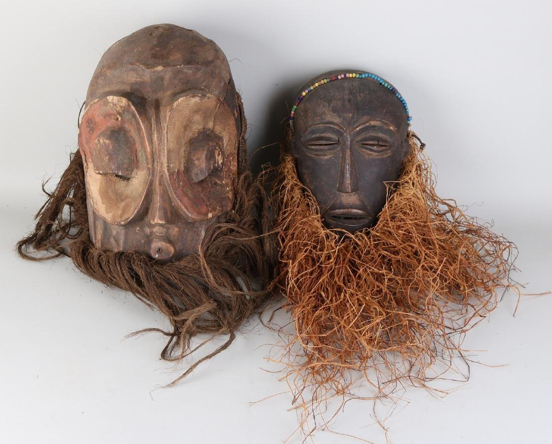 Two old polychromed African wood-carved masks with rope