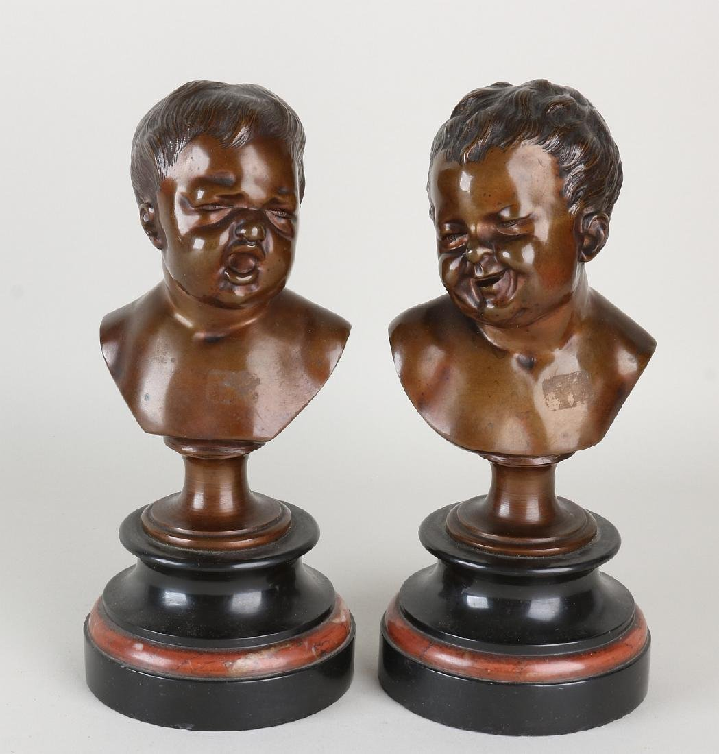 Two antique bronze busts on a marble base. Smiling and
