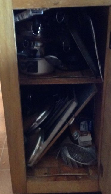 Cabinet full of pots, cookie sheets and more