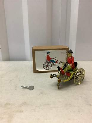 Man on trick cart tin toy