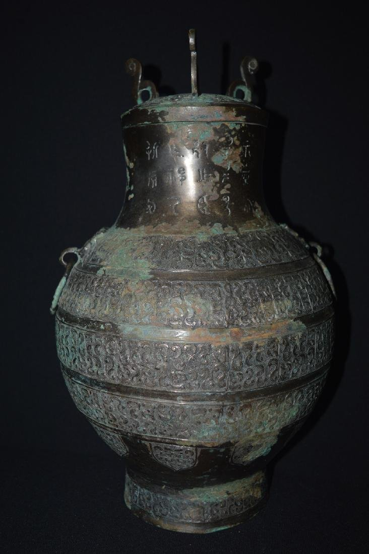 A BRONZE VASE WITH COVER
