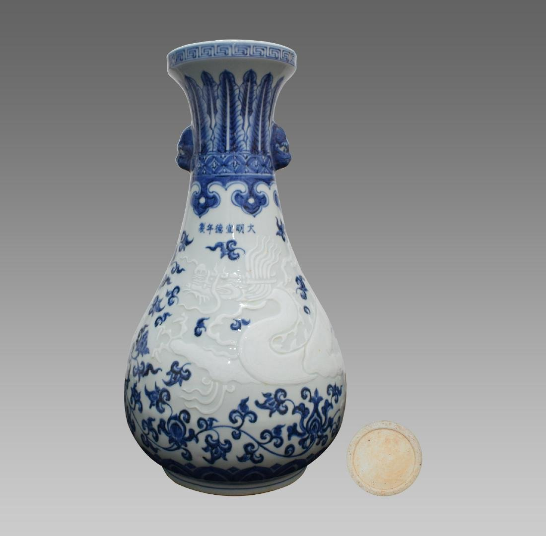 A BLUE AND WHITE CARVED DRAGON VASE