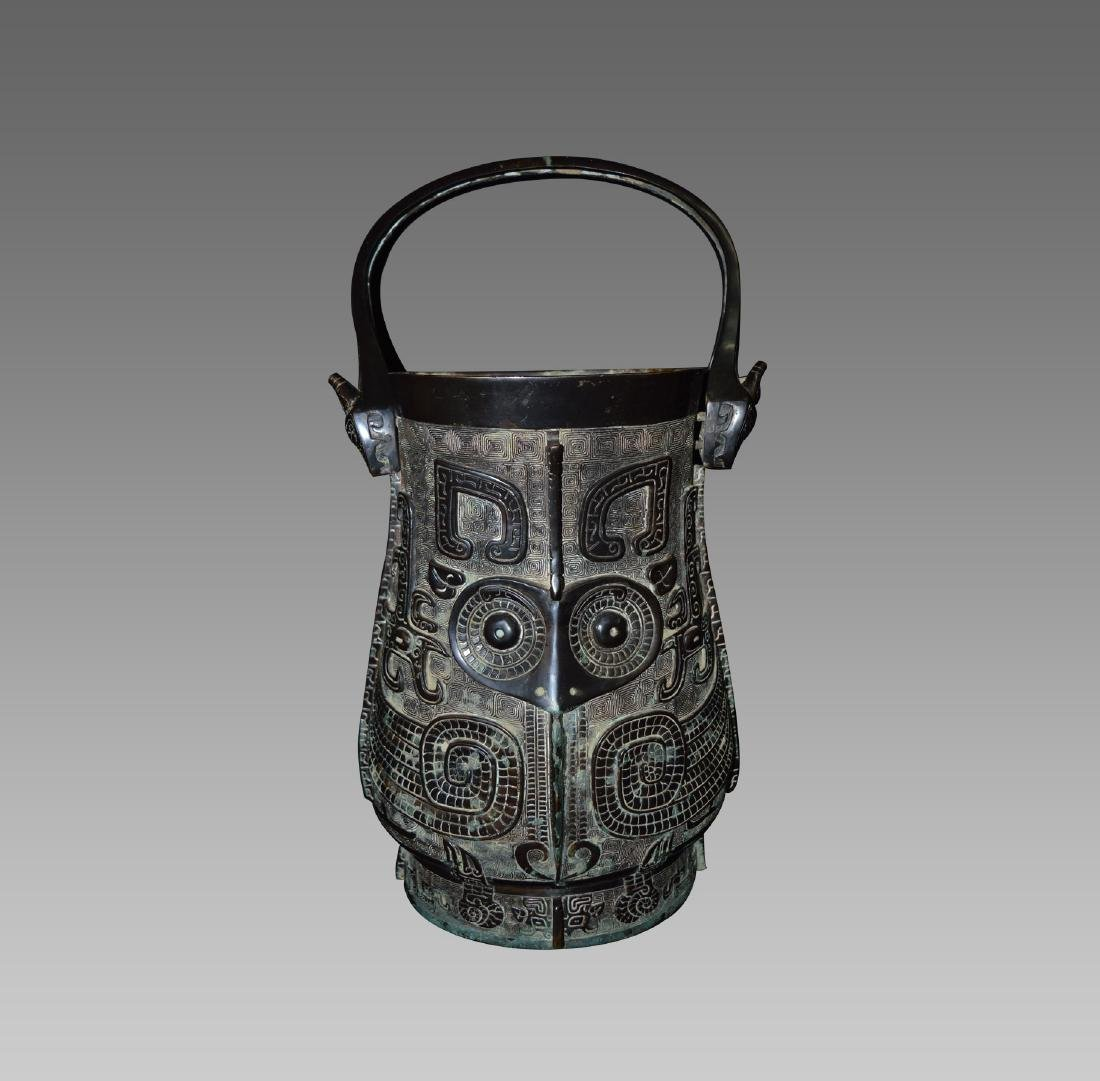 AN OLD BRONZE POT WITH HANDLE
