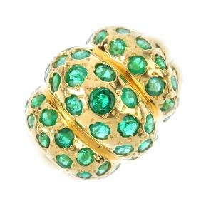An emerald dress ring. Comprising three-graduated