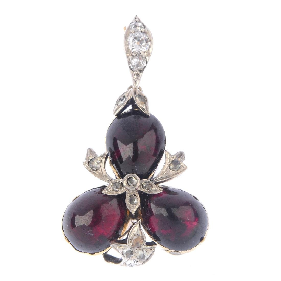 A garnet and diamond pendant. The pear-shape garnet