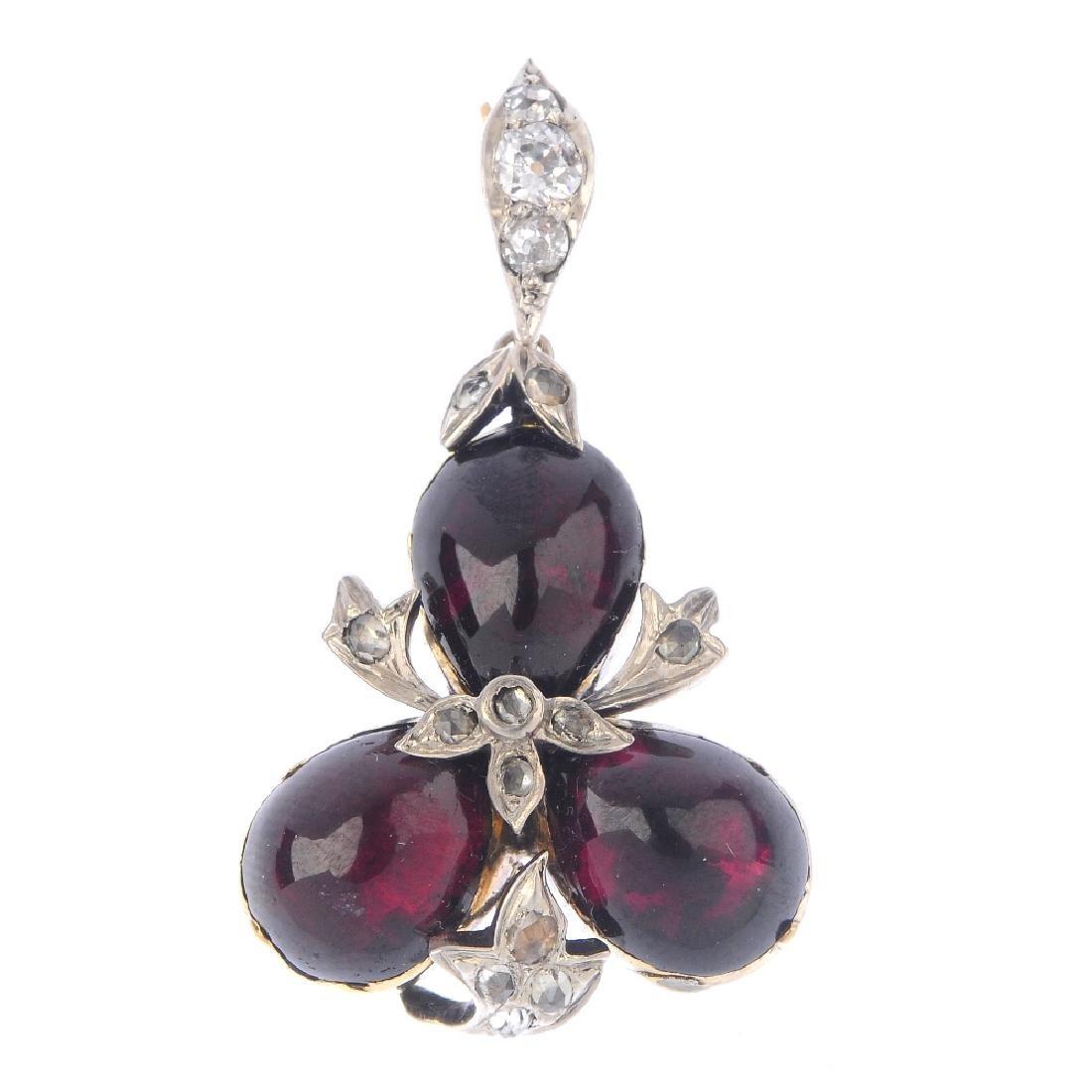 A garnet and diamond pendant. The pear-shape garnet