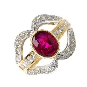 A 14ct gold ruby and diamond ring. The oval-shape ruby